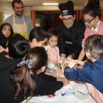 Familias y niños realizando los pinchos bajo la atenta mirada de Óscar Carbonell