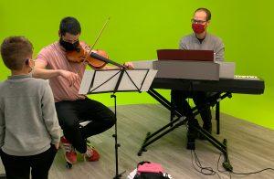 Músicos con piano y violín siendo oservados por un niño sordo