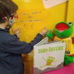 Niño escribiendo en una cartulina